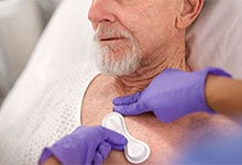 An older patient in a hospital bed has a sensor placed on his chest.